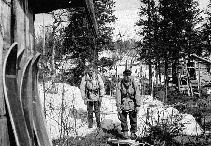 Her er Ola Holen (til venstre) og Kaare Bredesen tilbake i «Ambassaden», Grebegruppas hovedkvarter i Ruudshytta. De er utstyrt med tunge sekker, alltid rundt 40 kilo, våpen, og treski som ikke alltid gled like godt i djuprent og våt snø rundt påsketider i 1945.